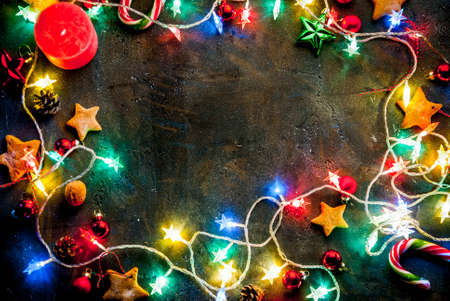 Christmas dark blue background with christmas garland, decorations, gingerbread stars  and candles.  Top view copy space frame