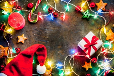 Christmas dark blue background with christmas garland, decorations, gingerbread stars, gift box and santa hat  and candles.  Top view copy space frame Stockfoto