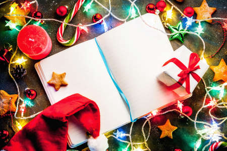 Christmas dark blue background with christmas garland, decorations, gingerbread stars, gift box and santa hat  and candles.   Top view copy space, with notepad for wishing Stockfoto