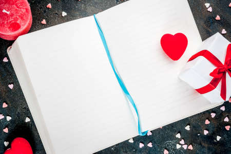 Valentines Day concept, background for congratulations with a notepad, pen and decorative sweet hearts, a red candle. Top view copy space Stockfoto