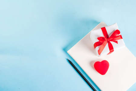 Valentines day light blue background. Red heart, gift, notepad and pencil. Greeting card concept. Top view copy space