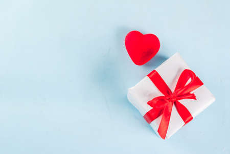 Valentines day light blue background with gift box with red ribbon and red heart. Greeting card concept. Top view copy space