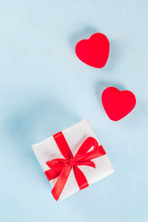 Valentines day light blue background with gift box with red ribbon and red hearts. Greeting card concept. Top view copy space