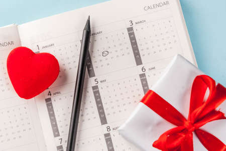Valentines day greeting card. Red heart with gift box over february calendar on light blue background. Copy space for greetings  top view