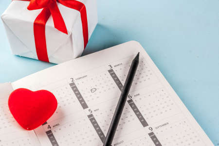 Valentines day greeting card. Red heart with gift box over february calendar on light blue background. Copy space for greetings