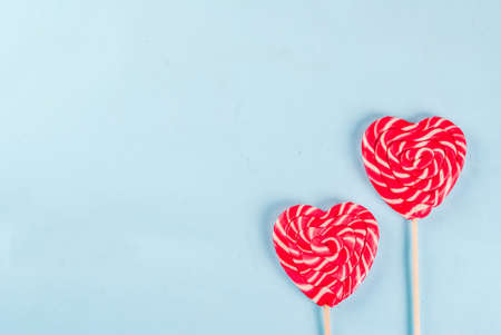Valentines day light blue background, greeting card concept, Two red heart lollipops or sweet candy on sticks,  top view copy space Stockfoto
