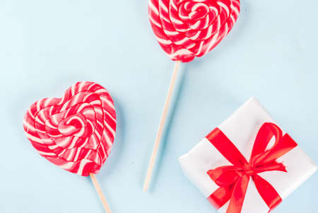 Valentines day light blue background, greeting card concept, Two red heart lollipops or sweet candy on sticks, with gift box, top view copy space Stockfoto