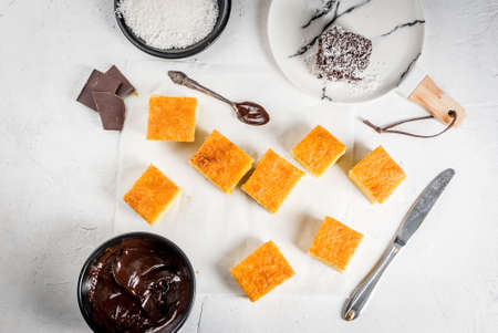 Australian cuisine. Preparation of traditional Australian dessert Lamington: biscuit in chocolate with coconut shaving powder. Top view. White table.