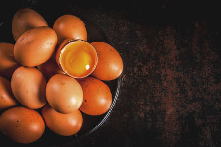 Organic farm chicken eggs, on a plate, on a dark rusty metal background, copy space top view Stock Photo