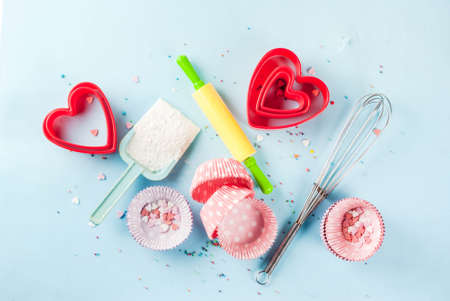 Sweet baking concept for Valentines day,  cooking background with baking - with a rolling pin, whisk for whipping, cookie cutters, sugar sprinkling, flour. Light blue background, top view copy space 스톡 콘텐츠