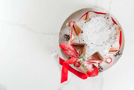 stock photo traditional italian christmas fruit cake panettone pandoro with festive red ribbon and christmas decorations on white background