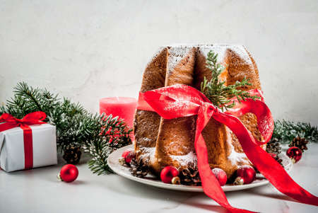 Traditional Italian Christmas fruit cake Panettone Pandoro with festive red ribbon and Christmas decorations, on white background, copy space