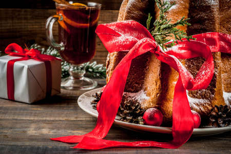 Traditional Italian Christmas fruit cake Panettone Pandoro with festive red ribbon and Christmas decorations, gift box and mulled wine, on wooden home background, copy space Foto de archivo - 91840793