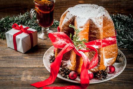 Tradicional Natal italiano bolo de frutas Panetone Pandoro com fita vermelha festiva e decorações de Natal, caixa de presente e vinho quente, no fundo de casa de madeira, copie o espaço Foto de archivo - 91840794