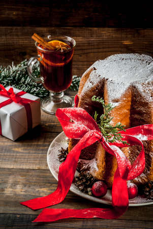 Traditional Italian Christmas fruit cake Panettone Pandoro with festive red ribbon and Christmas decorations, gift box and mulled wine, on wooden home background, copy space Foto de archivo - 91840795