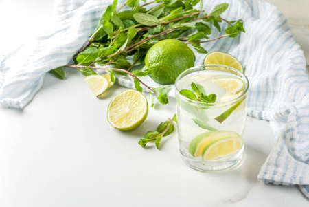 Homemade lemonade or mojito cocktail with fresh lime and mint leaves, white marble background, copy space