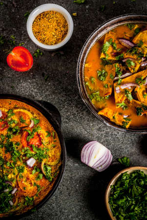 Indian food recipes, Masala Omelette with and Indian Omelet Masala Egg Curry, with fresh vegetables - tomato, hot chili pepper, parsley dark stone background, copy space top view Archivio Fotografico