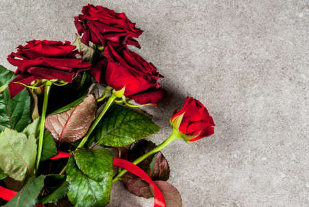Holiday  background, Valentines day. Bouquet of red roses, tie with a red ribbon, with wrapped gift box and red candle. On a gray stone table, copy space top view Stock Photo