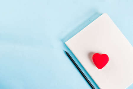 Valentines day light blue background. Red heart, notepad and pencil. Greeting card concept. Top view copy space