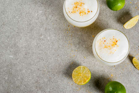 Peruvian, Mexican, Chilean traditional drink pisco sour liqueur, with fresh lime, on gray stone table, copy space top view