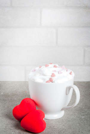 Romantic background, Valentines day. Cup for coffee or hot chocolate, with whipped cream and sweet hearts, with two plush red hearts,  copy space