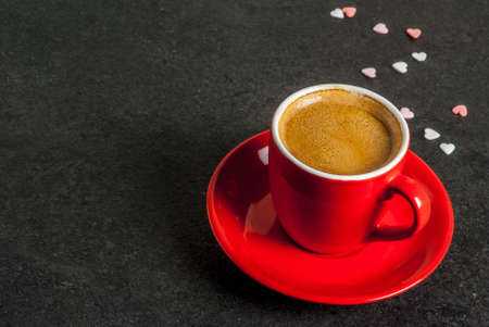 Valentine's day concept, coffee mug and sweet heart shaped sprinkles, black background, copy space