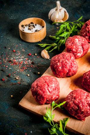 Ruwe vleesballetjes met olijfolie en kruiden op donkere betonnen tafel, kopie ruimte Stockfoto