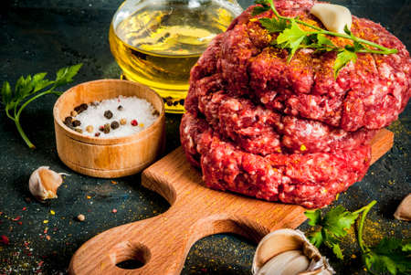 Raw burger cutlets with salt, pepper, oil, herbs and spice, on dark table, copy space Foto de archivo
