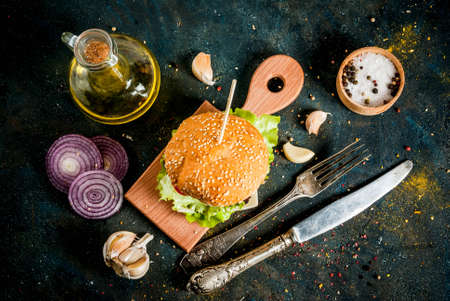 Fast food. Unhealthy food. Delicious Fresh Tasty Burger with Beef Cutlet, fresh Vegetables and Cheese on dark blue concrete background. Copy space top view Stock Photo