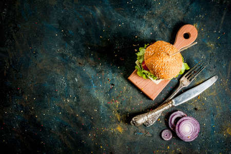 Fast food. Unhealthy food. Delicious Fresh Tasty Burgers with Beef Cutlet, fresh Vegetables and Cheese on dark blue concrete background. Copy space  top view Stock Photo