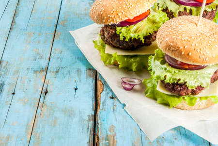 Picnic, Fast food. Unhealthy food. Delicious Fresh Tasty Burgers with Beef Cutlet, fresh Vegetables and Cheese on old rustic blue wooden table with sweet soda water. Copy space Stock Photo