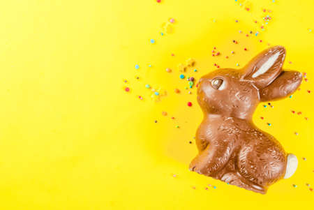 Easter background with chocolate rabbit and sugar sprinkling, on yellow background. Top view copy space. Spring holidays concept