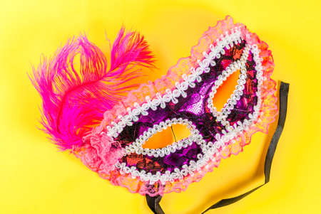 Mardi gras background with holiday mask, on bright yellow background copy space top view Stock Photo