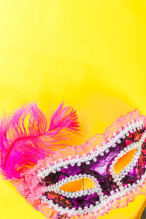 Mardi gras background with holiday mask, on bright yellow background copy space top view Imagens