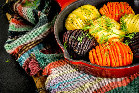 Ideas of vegan food, autumn recipes from vegetables. Roasted Hasselback Beets, carrots, potatoes, with fresh herbs, in a frying pan, on a black stone table, copy space