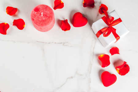 Valentines day background with rose flower petals, white wrapped gift box with red ribbon and holiday red candle, on white marble background, copy space top view