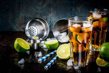 Cuba Libre, long island or iced tea cocktail with strong alcohol, cola, lime and ice, two glass, dark background copy space 스톡 콘텐츠