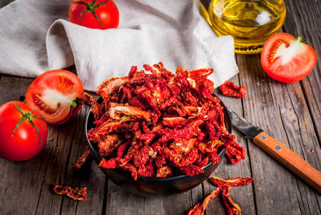 Homemade sun-dried organic tomatoes, crispy tomato chips, on an old rustic wooden table with fresh tomatoes and olive oil. Copy space