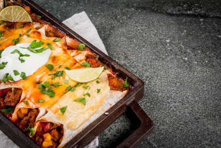Mexican food. Cuisine of South America. Traditional dish of spicy beef enchiladas with corn, beans, tomato. On a baking tray, on a black stone background. Copy space