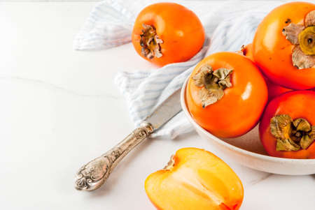 Delicious raw ripe persimmon fruit on white marble background copy space
