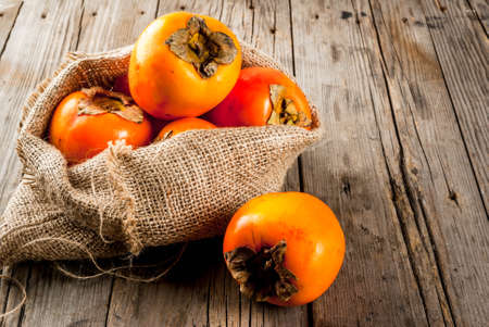 Delicious raw ripe persimmon fruit on old wooden background copy space