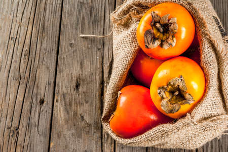 Delicious raw ripe persimmon fruit on old wooden background copy space top view
