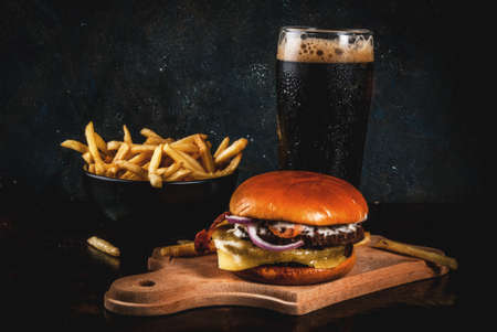 Fresh meat and cheese burger with French fries and glass of dark ginger beer, on dark blue background, copy space