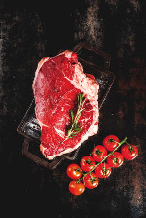 Fresh raw meat, lamb beef marble steak on a grill pan board, with ingredients for cooking. On dark rusty metal table, copy space top view Stok Fotoğraf