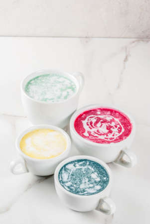 Organic vegan Latte coffee, decaffeinated - turmeric, beetroot, seaweed and matcha. On a white marble background, top view copy space
