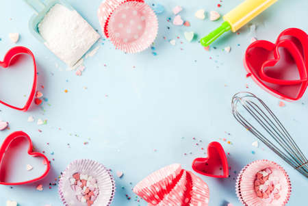 Sweet baking concept for Valentine's day,  cooking background with baking - with a rolling pin, whisk for whipping, cookie cutters, sugar sprinkling, flour. Light blue background, top view copy space