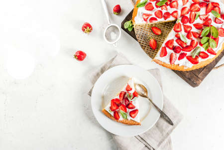 Homemade biscuit cake with whipped cream, fresh organic raw strawberries and mint. On a white stone table. Copy space top view