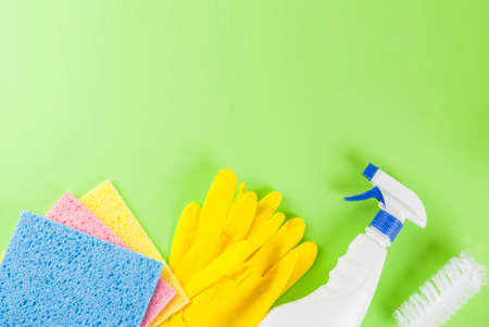 Spring cleaning concept with supplies, house cleaning products pile. Household chore concept, on green background top view copy space Stock Photo