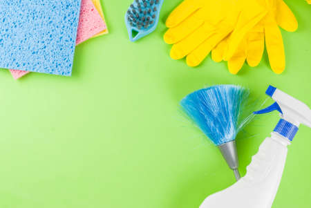 Spring cleaning concept with supplies, house cleaning products pile. Household chore concept, on green background top view copy space Zdjęcie Seryjne