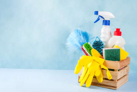 Spring cleaning concept with supplies, house cleaning products pile. Household chore concept, on light blue background copy space Stock Photo